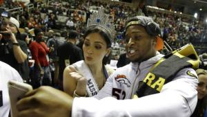 Miss Universe Pia Alonzo Wurtzbach poses for a cell phone photos with Denver Broncos outside linebacker Corey Nelson during Opening Night for the NFL Super Bowl 50 football game Monday, Feb. 1, 2016, in San Jose, Calif. (AP Photo/Marcio Jose Sanchez)