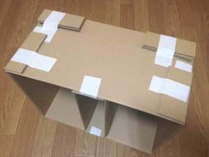 折り曲げたダンボール紙を大きい箱の上面または底面にガムテープで貼り付ける