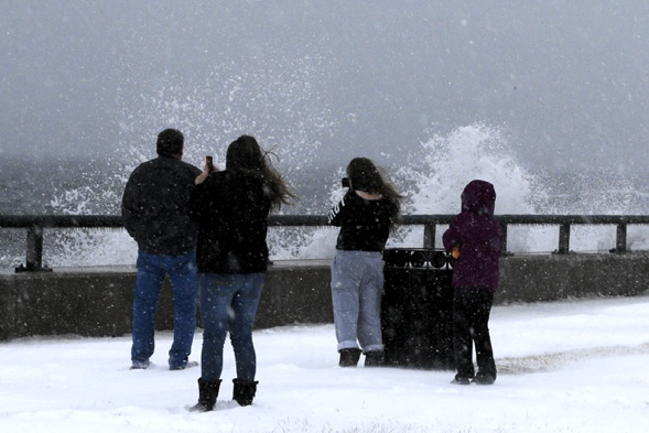 Onlookers look at waves crashing against the seawall around high tide during a winter nor'easter snowstorm in Lynn, Massachusetts January 2, 2014. (Reuters/Brian Snyder)