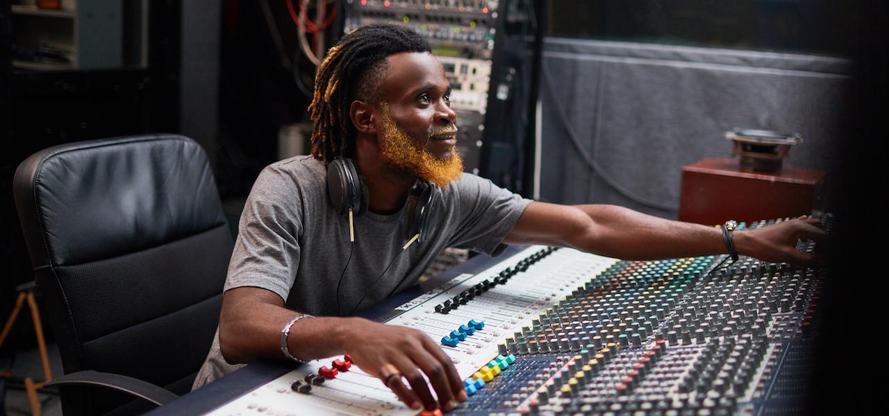 Modern deejay regulating sounds in mixer