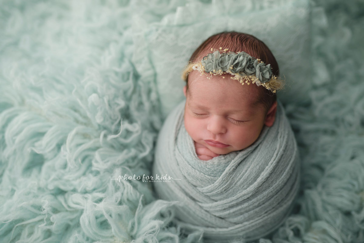 new born baby girl in green wrap and flowers diadem during a photo session in photography workshop by Nicoleta Raftu