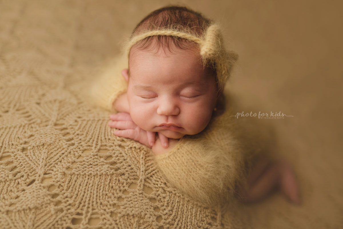 new born girl sleeps on her belly and poses during a photo shooting in a photography workshop by Nicoleta Raftu
