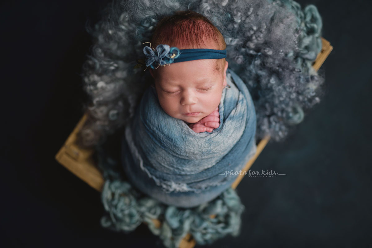 new born little girl in blue outfits sleeps on her back during a photography workshop by Nicoleta Raftu