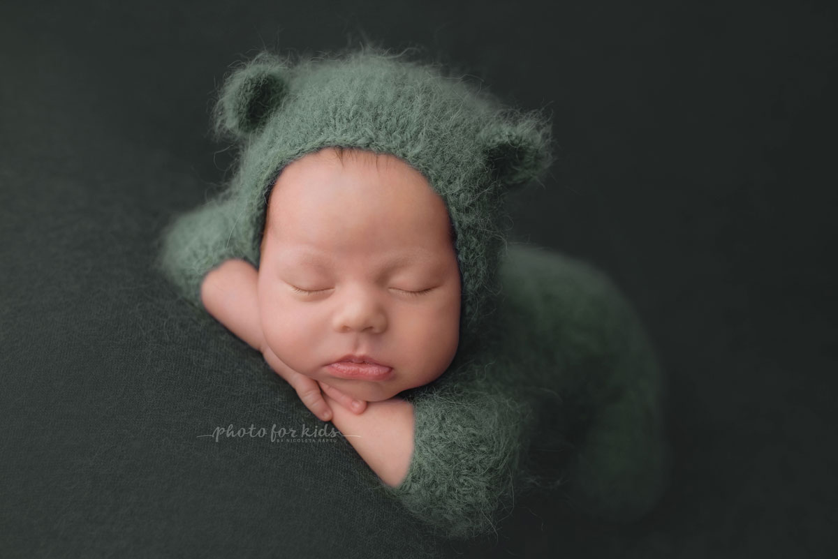 newborn in green outfits sleeps during a photo shooting in a workshop by Nicoleta Raftu