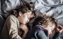 Two children sleeping with sweaters on