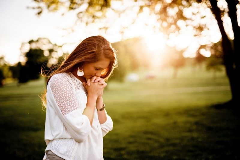 Woman folding her hands in prayer and looking down. Greenery is in the background.