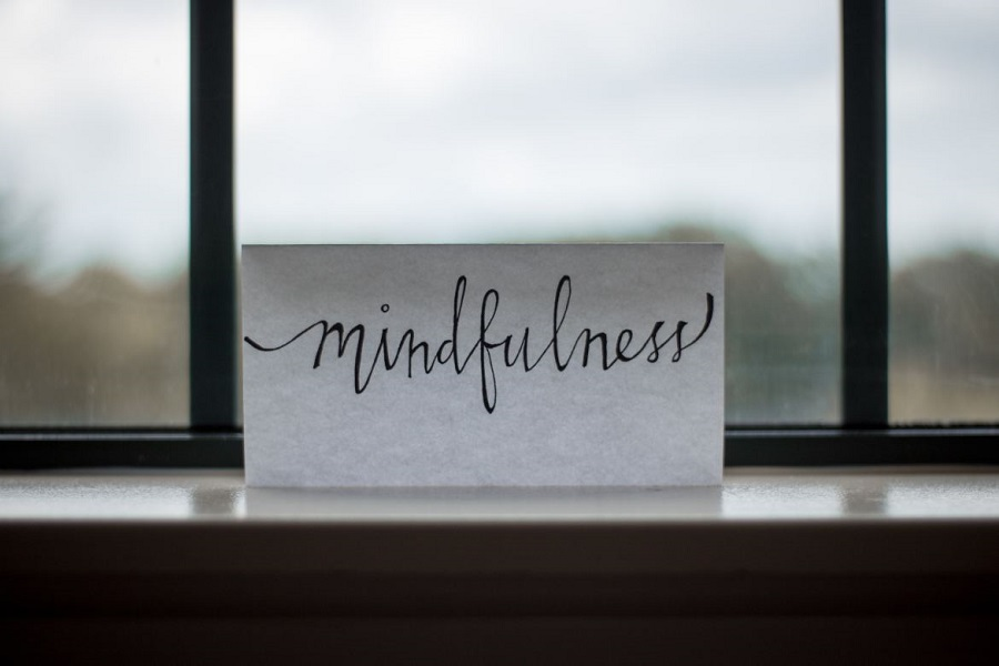 white paper with mindfulness written on it in front of a window