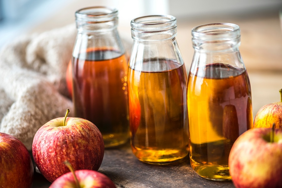 Apple juice in three glass containers surrounded by red and yellow apples and a sweater