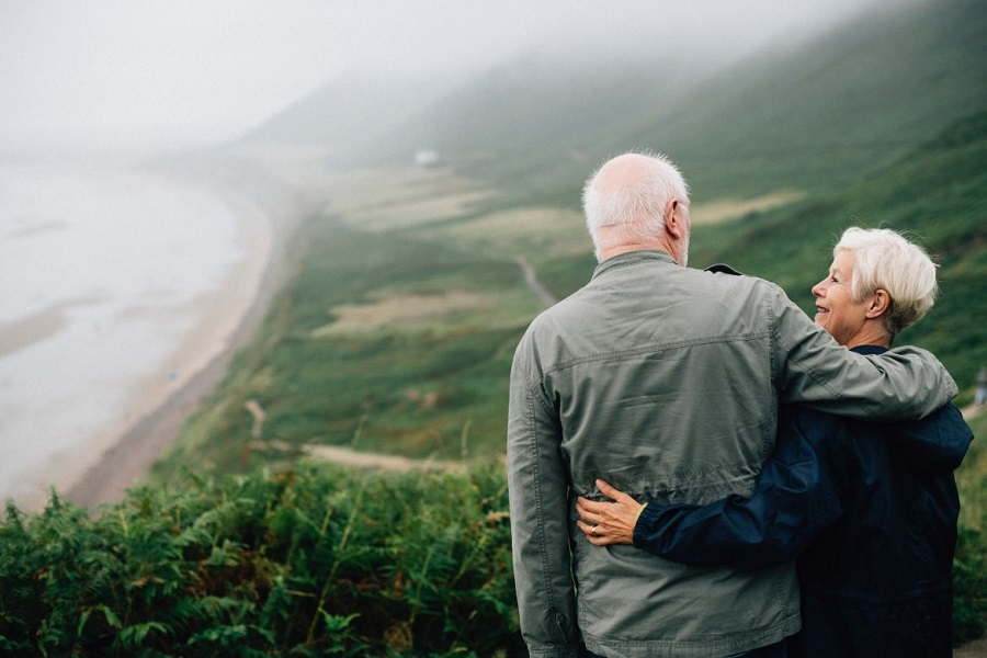 An older couple arm in arm looking at each other with greenery in the background