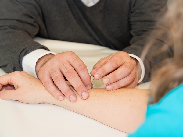 Man putting acupuncture needle in a woman's arm