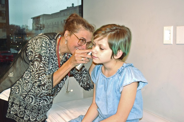 Woman using tool to look in child's ear