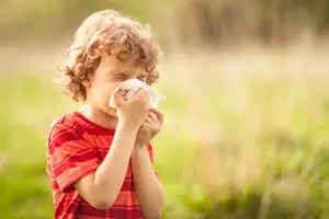 Boy blows his nose in a field of flowers due to allergies