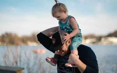 Father lifts a little girl onto his shoulders.