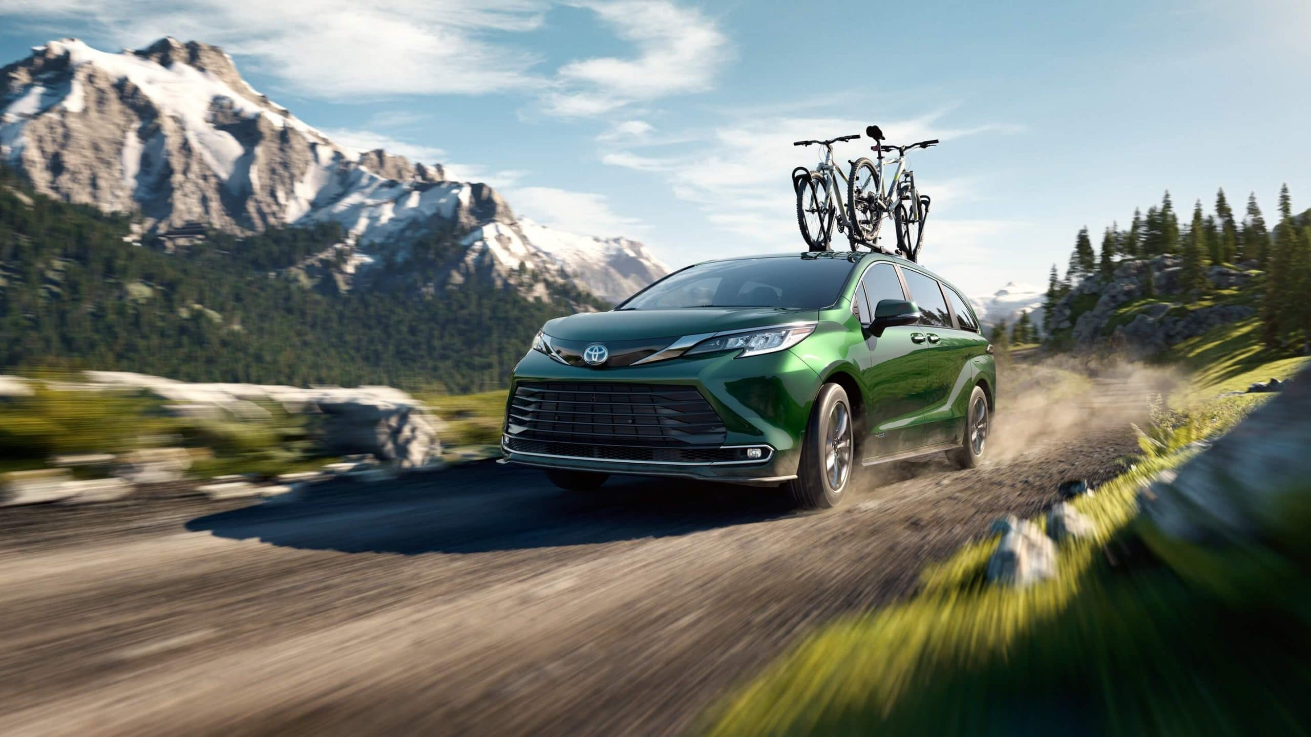 New Toyota Sienna driving off-road with bikes attached to the roof rack