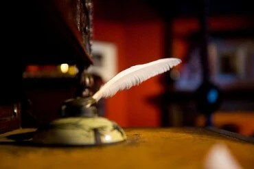 Photograph of quill pen on desk by Ross Pollack