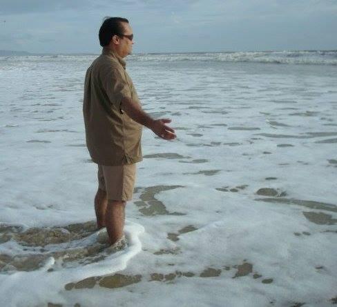 Joygopal with sunglasses greeting the sea.