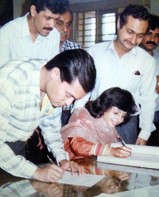 Photo of Priti and Joygopal Podder signing marriage documents