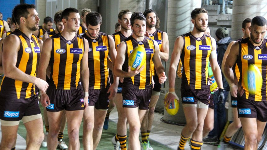Isaac Smith (centre) with ball about to lead his team onto the field for his 100th AFL game