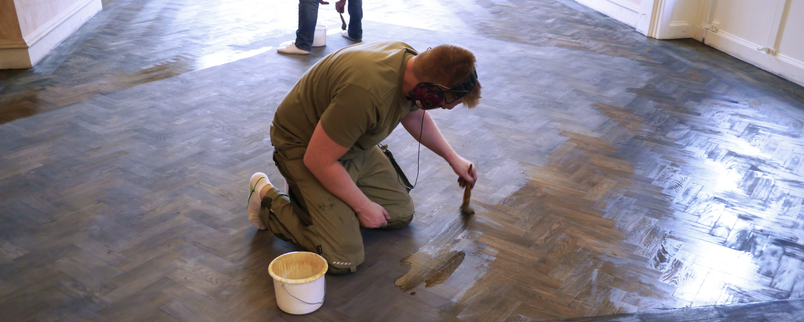 man sealing floor stain with shellac using traditional brush