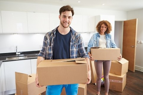 couple holding boxes as if moving in. This image is meant to portray couples communication skills in Massachusetts.