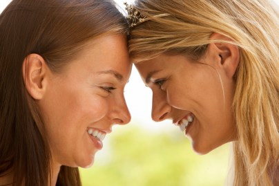 Young lesbian couple smiling at each other, feeling emotionally connected. Hold Me Tight Workshops help rebuild trust and save a marriage.