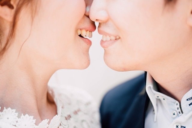 Close up photograph of lesbiancouple kissing during a formal event. Image meant to represent emotional connection and the ability to resolve conflicts when a couple attends a couple and marriage retreat with New England Hold Me Tight.