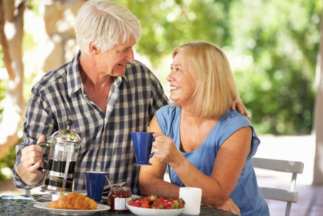 Older couple sharing meal happily. Image is meant to represent the happiness a couple feels after attending a marriage seminar in New England or a marriage retreat in New England.