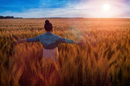Girl spreading arms wide in open field of wheat. This image is meant to portray feeling good relationship connection after attending marriage counseling retreats in New England or intensive marriage counseling in Massachusetts.