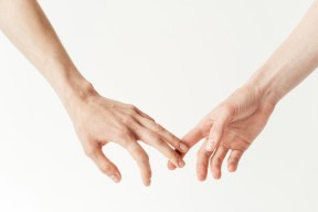 Closeup of a lesbian couple touching fingers. This image is meant to portray improving emotional connection and communication after attending an EFT marriage intensive for lesbians or intensive marriage counseling for lesbians.
