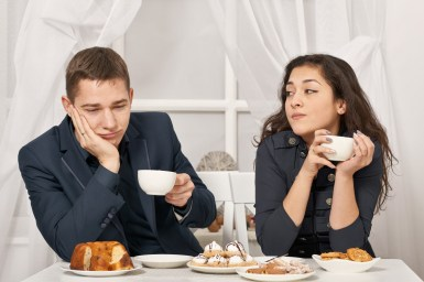 Couple looking at each other unhappily over dessert. This image is meant to portray the disconnection a couple can change when they get relationship help from a Hold Me Tight Retreat in Massachusetts.