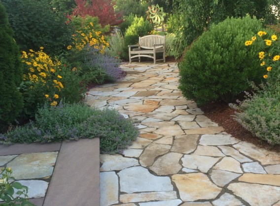 Stone walkway with garden beds on both sides, leading up to a bench. This image is meant to represent emotional connection and the ability to rebuild trust after attending a Hold Me Tight Workshop with Bri McCarroll of New England Hold Me Tight.