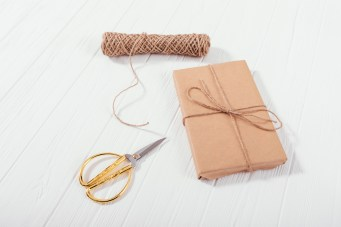 paperwrapped box with scissors and string closeby.  Image meant to portray therapy in a box or self-help for couples.