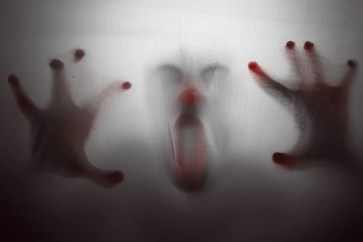 Image of clown screaming behind filmy glass. This image is meant to portray how scary it is when we are in distress in our relationships.