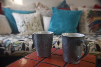 Image of two coffee cups in front of a day bed with pillows.  Image is meant to portray Private Couples and Marriage Intensives with Hold Me Tight New England and Bri McCarroll.