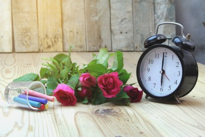 Alarm clock with roses on old wood. Signifies creatively expressing love after attending emotionally focused intensive couples therapy in Massachusetts or just normal emotionally focused couples therapy in Massachusetts.