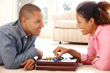 Interracial couple playing game, smiling. This signifies better communication and emotional connection after attending intensive marriage counseling Massachusetts.
