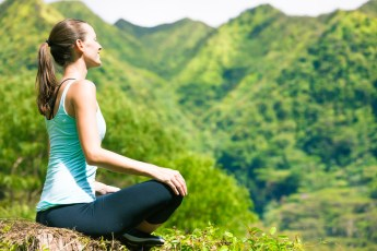 Woman on hill meditating. Signifies emotional connection and balance from attending intensive relationship therapy for lesbians.
