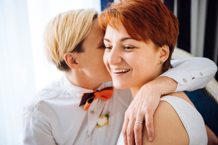 Lgbt couple, an apparently lesbian couple, being physically close with one whispering in the other's ear. Signifying better communication after attending intensive relationship therapy for lesbians or lesbian couples counseling retreat, in ma.