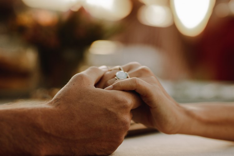 Cropped shot of couple holding hands sitting at table. This signifies renewing and rebuilding emotional connection in a burned out marriage.