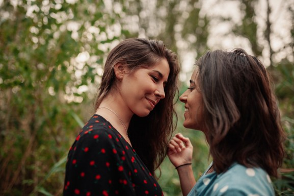 Young lesbian couple or LGBT couple looking at each other lovingly. This signifies emotional connection and better communication in their relationship due to attending a Hold me tight private retreat.