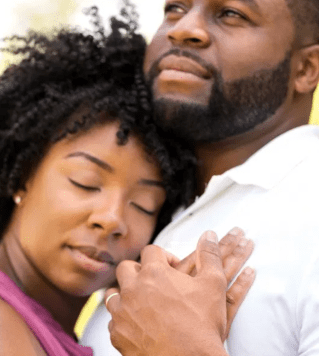 Black couple lovingly hugging one another.  This signifies emotional connection from attending a private couples retreat or couples therapy intensive.