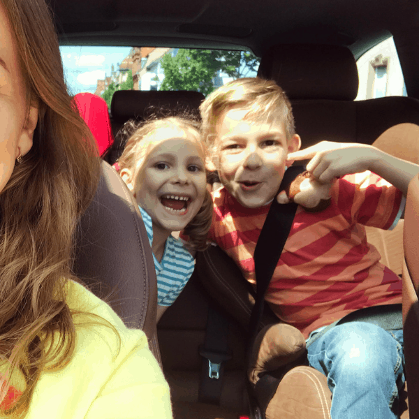 kids and mom in a car for a road trip with an apple snack
