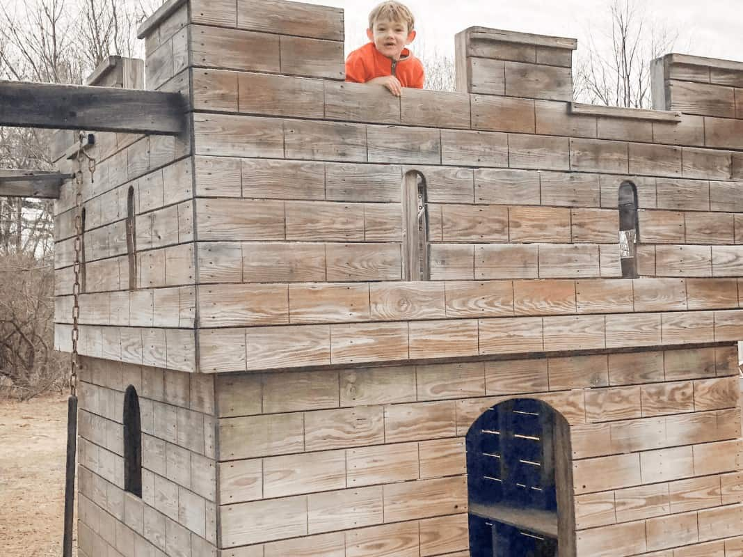little boy playing in a castle shaped play area at Animal Adventures in Bolton, MA