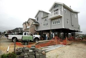 Homes being lifted after flood damage