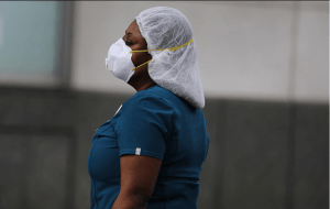 A woman wears a face mask, Scrubs, and hair covering PPE