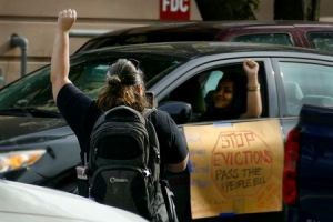 """two women with a fist in the air - one on foot one in a car, a sign on the car says """"STOP EVICTIONS"""""""