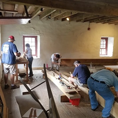 Volunteers assisting with the prep and layout of stock for the Millwright's Shop's workbench