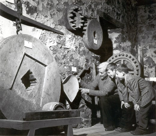 E. Mortimer Newlin kneeling next to two children, showing them a wooden grain shovel and other old milling equipment.