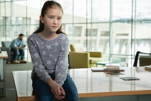 Image of young girl looking sad in a library