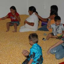 Meanwhile, how about playing in a corny sandbox. Check out the foreground. It wasn't until I viewed this photo at home that I saw the kid buried entirely in corn except for his face. He appears to be smiling?!